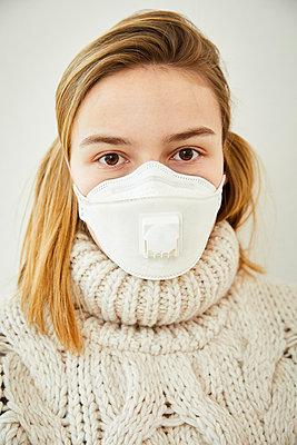 Portrait of blond woman wearing FFP2 mask at home - p300m2188588 by Sandra Bielmeier