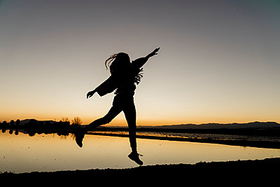 Carefree young woman with arms raised dancing during dusk at Ebro Delta, Spain - p300m2250089 by VITTA GALLERY