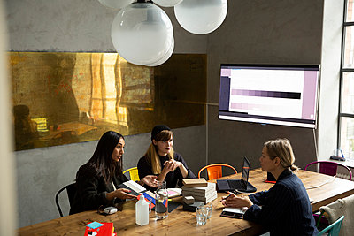 Businesswoman with female colleagues discussing over color swatch in conference room - p426m2270436 by Maskot