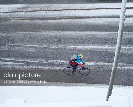 Fahrradfahrer auf verschneiter Straße - p1124m1090502 von Willing-Holtz