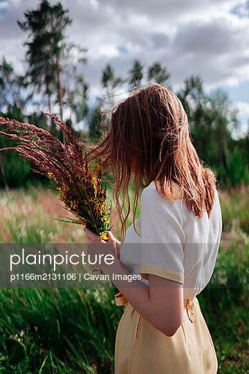 A young woman stands in the tall grass with a bouquet of flowers - p1166m2131106 by Cavan Images