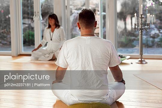 Man practicing yoga in class - p312m2237181 by Plattform