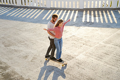 Young couple having fun with longboard - p1124m1503642 by Willing-Holtz