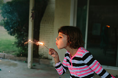 Girl blowing burning sparkler while playing in backyard - p1166m1403078 by Cavan Images