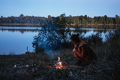 Side view of woman sitting by campfire and lake in forest - p1166m2025326 by Cavan Images