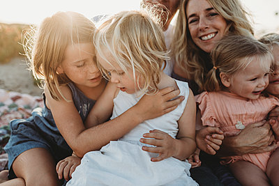 Lifestyle close up of family with young sisters sitting on beach - p1166m2165886 by Cavan Images