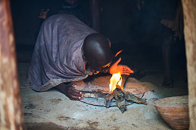 Africa, Namibia, Girl makes fire in a hut - p1167m2272276 by Maria Schiffer