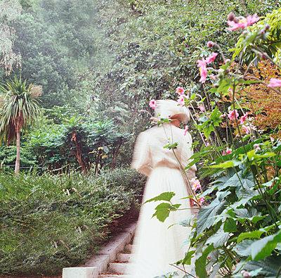 Woman in white dress in wild garden - p1311m1136870 by Stefanie Lange