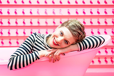 Woman lying in a bathtub in front of pink coloured background - p1332m2055058 by Tamboly