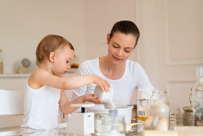 Mother and little daughter making a cake together in kitchen at home - p300m2102634 by Daniel Ingold