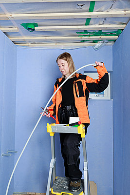 Young woman renovating house - p312m2262563 by Phia Bergdahl