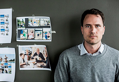 Portrait of serious businessman standing against wall in office - p426m811559f by Maskot