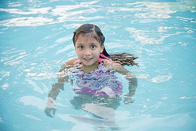 Smiling Hispanic girl in swimming pool - p555m1304011 by Jeff Greenough