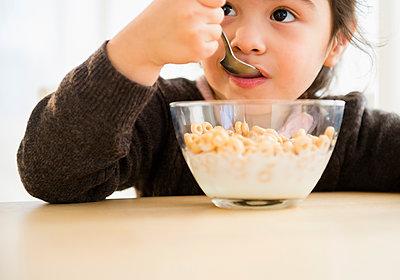 Hispanic girl eating bowl of cereal - p555m1419887 by JGI/Jamie Grill