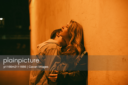 Young couple romancing in city at night - p1166m2111666 by Cavan Images
