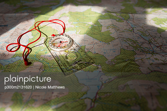 Compass on map, Scotland, UK - p300m2131620 by Nicole Matthews