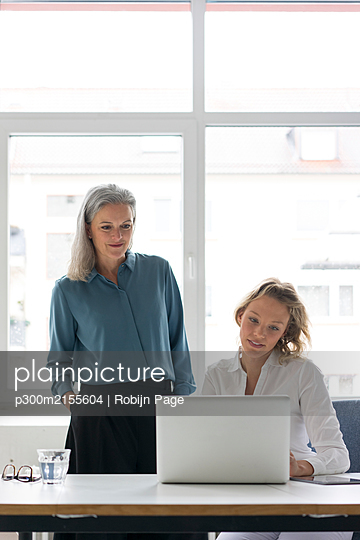Two businesswomen using laptop at desk in office together - p300m2155604 by Robijn Page