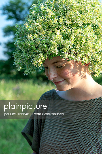 Portrait of smiling young woman wearing headpiece of flowers - p300m2156646 by Petra Stockhausen