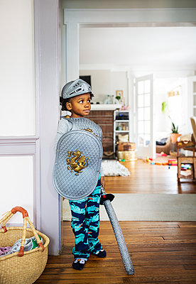 Full length of thoughtful boy dressed up in armor costume standing at home - p1166m1140351 by Cavan Images