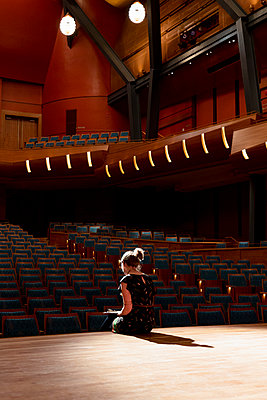 Female performer reviewing notes on stage in empty auditorium - p1192m2123237 by Hero Images