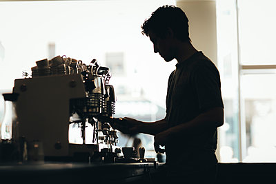 Silhouette of Barista preparing coffee in a coffee bar - p300m2012919 by Oriol Castelló Arroyo