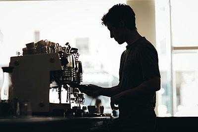 Silhouette of Barista preparing coffee in a coffee bar - p300m2012919 von Oriol Castelló Arroyo