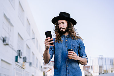 Fashionable young man with disposable coffee cup using mobile phone against clear sky - p300m2240301 by Eva Blanco
