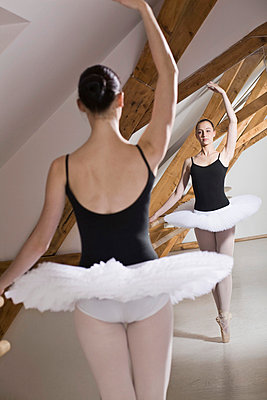 A ballet dancer on pointe with one arm raised in front of a mirror in a ballet studio - p30110700f by Iris Friedrich