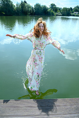 Woman in summer dress jumps into the lake - p427m2210859 by Ralf Mohr