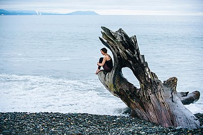 Mature woman sitting on large driftwood tree trunk at beach - p924m1054038f by Pete Saloutos