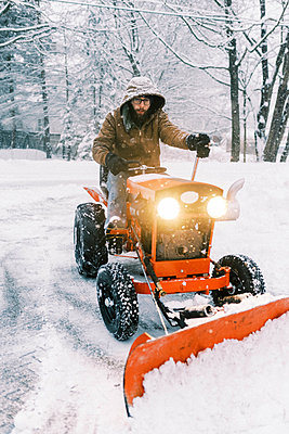 Man on a tractor plowing snow in a driveway during a nor'easter storm - p1166m2248928 by Cavan Images