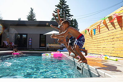 Brothers and sister jumping into sunny, summer swimming pool - p1192m2129476 by Hero Images