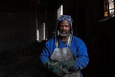 Male worker standing in foundry - p1315m2062636 by Wavebreak