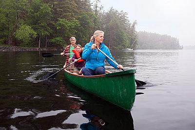 Grandparents and grandchildren canoeing on Kezar Lake on foggy day - p1424m1501008 by Monica Donovan