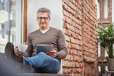 Man holding coffee cup while using digital tablet at home - p300m2273831 by Studio 27
