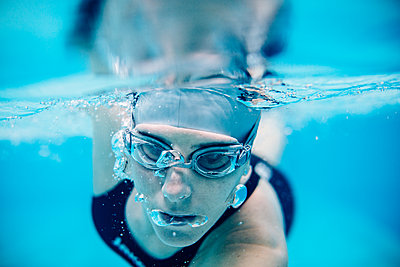 Underwater close up view of woman swimming - p429m1175335 by Sofie Delauw