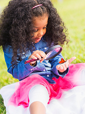 Mixed race girl examining butterfly with magnifying glass - p555m1420276 by JGI/Daniel Grill