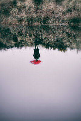Reflection in water of woman standing on lake shore holding red umbrella  - p597m2063513 by Tim Robinson