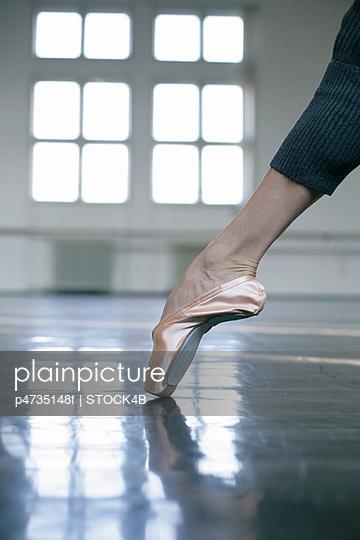 A female ballet dancer wearing a ballet shoe
