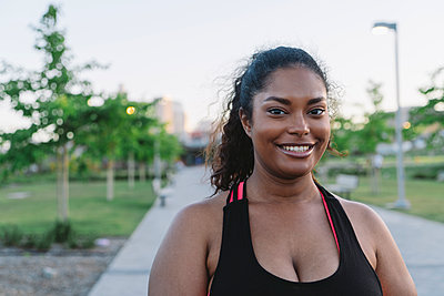 Portrait of happy sportswoman at park - p1166m1486265 by Cavan Images