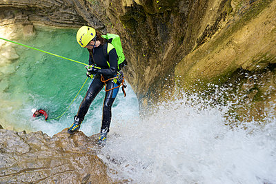High angle view of hikers rappelling amidst waterfall on canyons - p1166m2113024 by Cavan Images