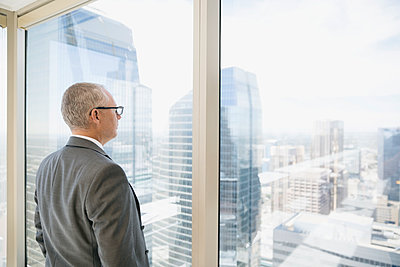 Pensive businessman looking at cityscape view at urban office window - p1192m1183765 by Hero Images