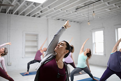 Focused woman practicing yoga reverse warrior pose in yoga class - p1192m1583333 by Hero Images