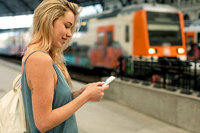Smiling young woman using cell phone at the train station - p300m2070409 by Mauro Grigollo
