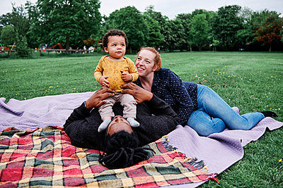 Happy family relaxing with son while lying on picnic blanket at park - p300m2287363 by Angel Santana Garcia