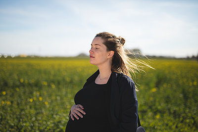Pregnant woman contemplating in meadow - p312m1533583 by Depiction AB