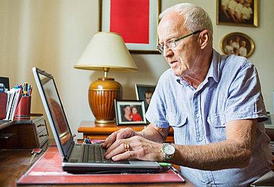 Senior man using laptop at home - p426m896752f by Maskot