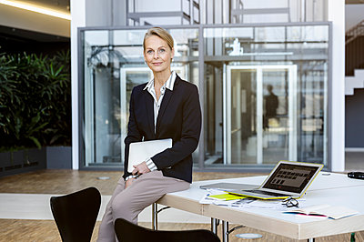 Portrait of business woman sitting on desk looking at camera smiling - p429m1578440 by suedhang photography