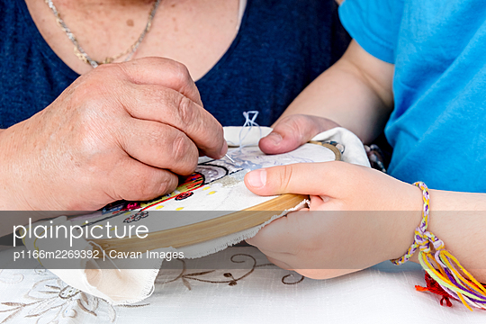 Close-up of the hands of a girl and her grandmother making an embroide - p1166m2269392 by Cavan Images