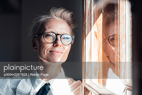 Smiling mature businesswoman looking away while leaning at window in home office - p300m2267823 by Robijn Page